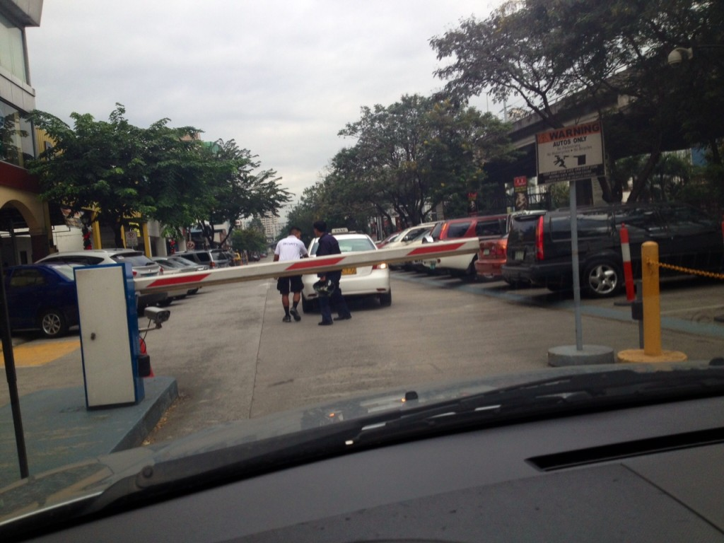 Together with one security personnel, the Good Samaritan in Blue Uniform pushes the taxi into the parking lot for fixing